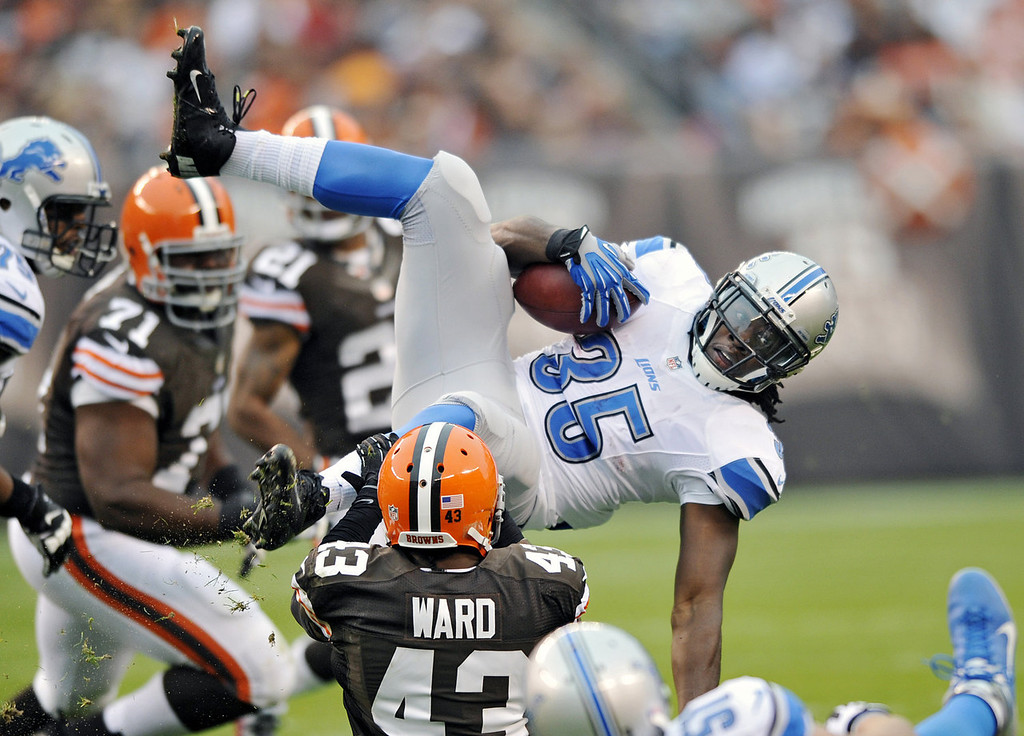 . Detroit Lions running back Joique Bell (35) is tripped up by Cleveland Browns strong safety T.J. Ward (43) after an 8-yard gain in the first quarter of an NFL football game Sunday, Oct. 13, 2013 in Cleveland. (AP Photo/David Richard)