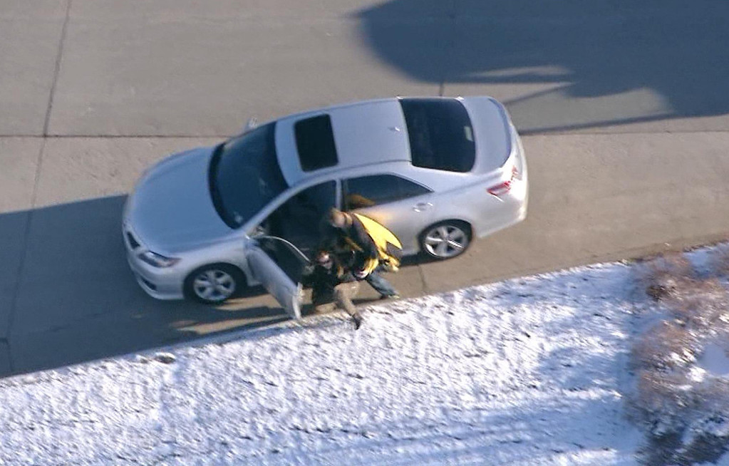 . In this image taken from video provided by CBS-4 TV Denver, Ryan Stone, 29, forces a woman from her car, which he then stole and drove off in Wednesday, March 12, 2014,  in  Lone Tree, Colo. Stone, suspected of stealing an SUV with a 4-year-old boy inside, carjacking two other vehicles and seriously injuring a state trooper was arrested Wednesday after police tracked him, and at times chased him, around the Denver area during morning rush hour.  (AP Photo/CBS-4 TV Denver)