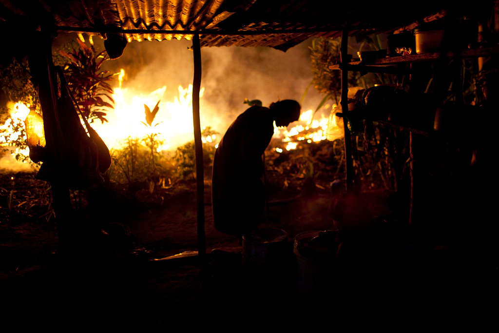 . In this Sept. 26, 2013 photo, an Ashaninka Indian woman is silhouetted against a wall of flames caused by burning branches during a land clearing in Otari Nativo, Pichari district, Peru. Otari, one of 350 Ashaninka communities, lies in the Apurimac river valley, the No. 1 coca-producing valley in the world. Most inhabitants grow coca and chew it as their ancestors have. But they also resist efforts to fell their forests to plant coca for commercial use. (AP Photo/Rodrigo Abd)