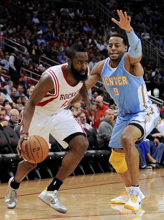 . Houston Rockets\' James Harden (13) drives against Denver Nuggets\' Andre Iguodala (9) in the second half of an NBA basketball game Wednesday, Jan. 23, 2013, in Houston. Denver won 105-95. (AP Photo/Pat Sullivan)