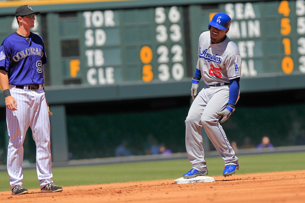 . Los Angeles Dodgers\' Carl Crawford (25) comes up lame after hitting a double with Colorado Rockies\' DJ LeMahieu (9) looking on during the third inning of the MLB National League baseball game Saturday June 1, 2013 in Denver. (AP Photo/Barry Gutierrez)