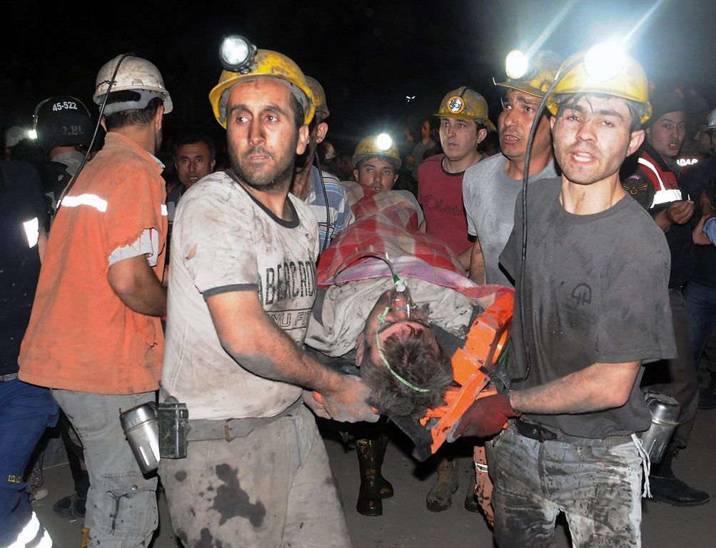 . Miners carry a rescued miner after an explosion and fire at a coal mine killed at least 17 miners and left up to 300 workers trapped underground, in Soma, in western Turkey, Tuesday, May 13, 2014. (AP Photo/Depo Photos)