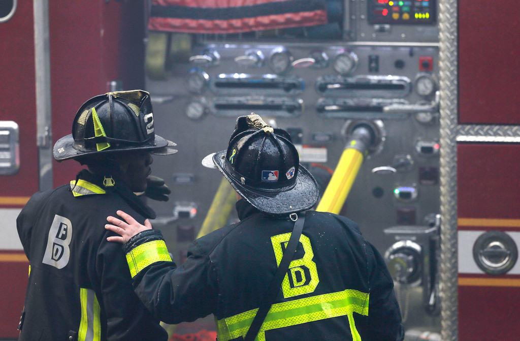 . A firefighter places his hand on the shoulder of another at the scene of a multi-alarm fire at a four-story brownstone in the Back Bay neighborhood near the Charles River, Wednesday, March 26, 2014 in Boston. (AP Photo/Steven Senne)