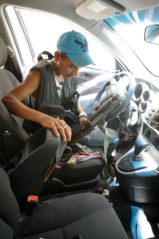 . A young man, who identifies himself as M3, grabs his weapon as he leaves his vehicle in the town of Aguililla, Mexico, Thursday, July 25, 2013. The 18-year-old, who claims on a video posted on a national newspaper website, that he is a former Templar Knights gunman who deserted the cartel and joined the ranks of the Aguililla self-defense group because he was disgusted with the way the Templar Knights treat the community. (AP Photo/Gustavo Aguado)