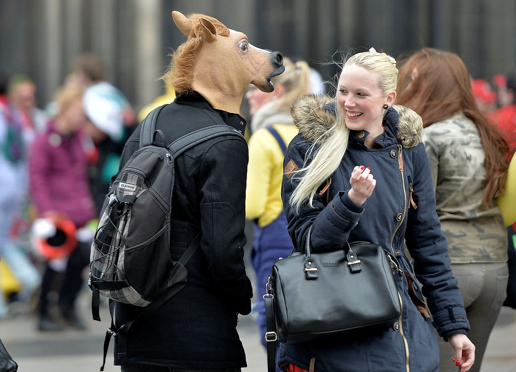 ". A woman smiles at a man with a horse head when tens of thousands of revelers dressed in carnival costumes celebrate the start of the street-carnival on the so called ""Old Women\'s Day\"" in the party capital Cologne, Germany, Thursday, Feb. 27, 2014. (AP Photo/Martin Meissner)"