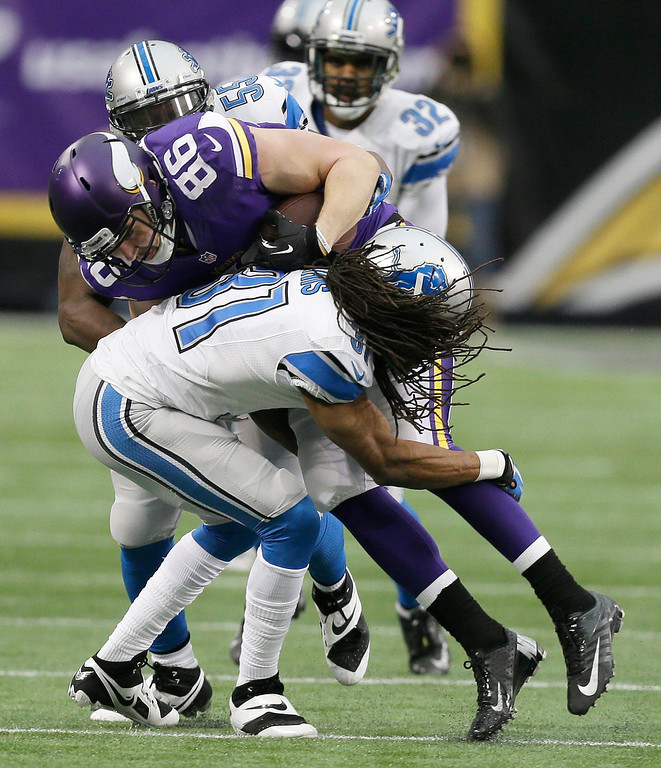 . Minnesota Vikings tight end Chase Ford (86) is tackled by Detroit Lions cornerback Rashean Mathis (31) after making a reception during the first half of an NFL football game, Sunday, Dec. 29, 2013, in Minneapolis. (AP Photo/Charlie Neibergall)