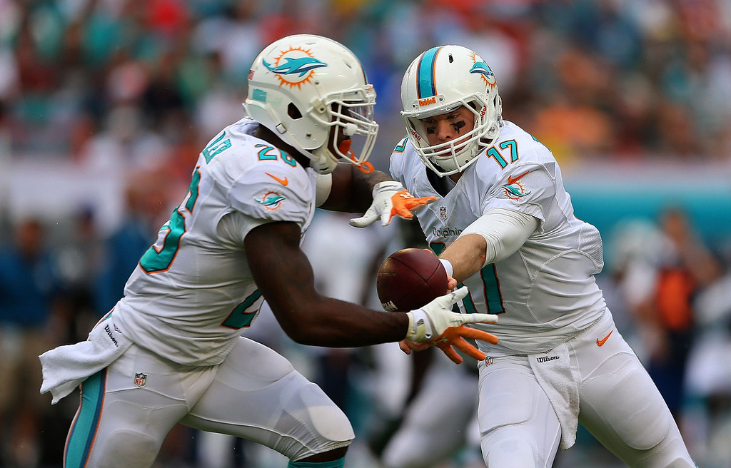 . Ryan Tannehill #17 of the Miami Dolphins hands off to Lamar Miller #26 during a game against the New York Jets at Sun Life Stadium on December 29, 2013 in Miami Gardens, Florida.  (Photo by Mike Ehrmann/Getty Images)