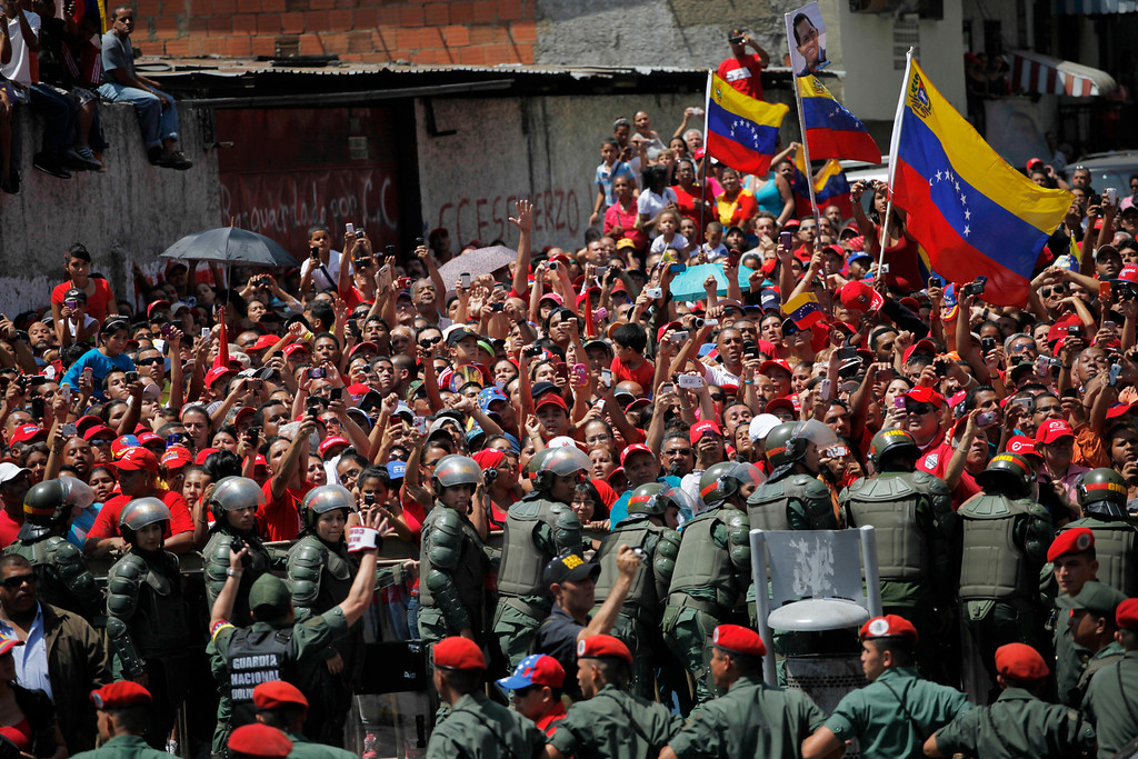 . Supporters of Venezuela\'s late President Hugo Chavez crowd the street to watch his coffin pass by as it is paraded from the hospital where he died on Tuesday to a military academy where it will remain until his funeral in Caracas, Venezuela, Wednesday, March 6, 2013. (AP Photo/Rodrigo Abd)