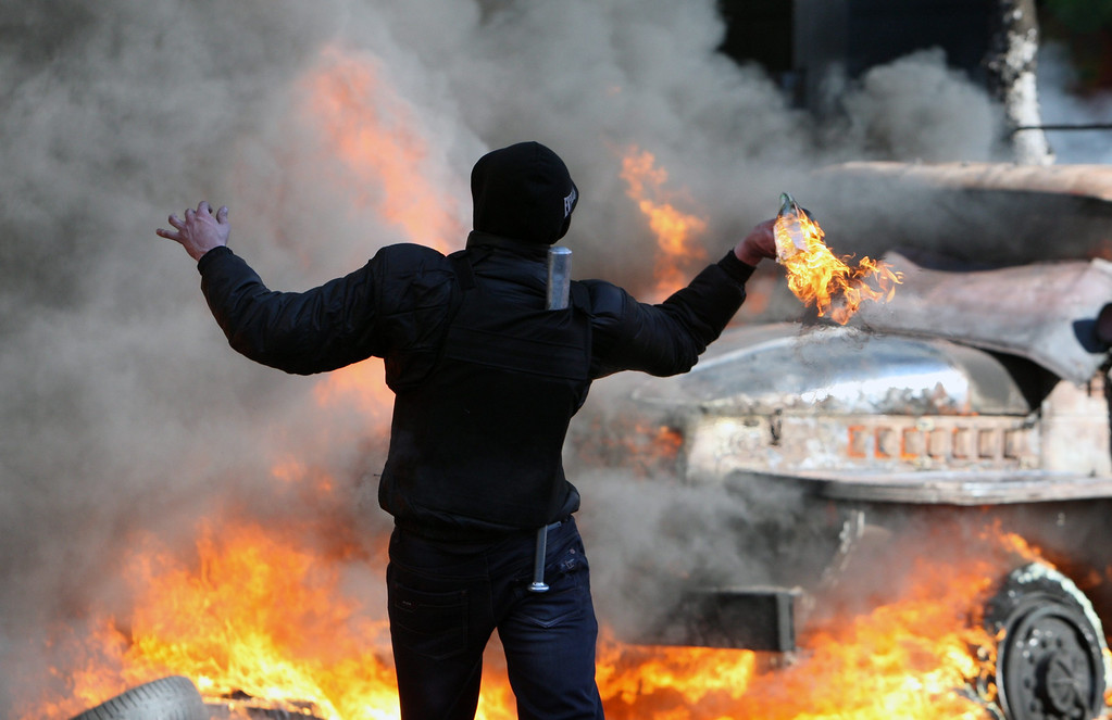 . An anti-government protester throws a molotov cocktail at police on the streets of downtown Kiev, Ukraine, 18 February 2014. EPA/IGOR KOVALENKO