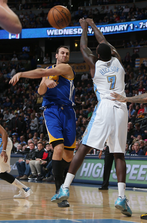 . Golden State Warriors center Andrew Bogut, left, of Australia, fires a pass as Denver Nuggets forward J.J. Hickson covers in the first quarter of an NBA basketball game in Denver, Monday, Dec. 23, 2013. (AP Photo/David Zalubowski)