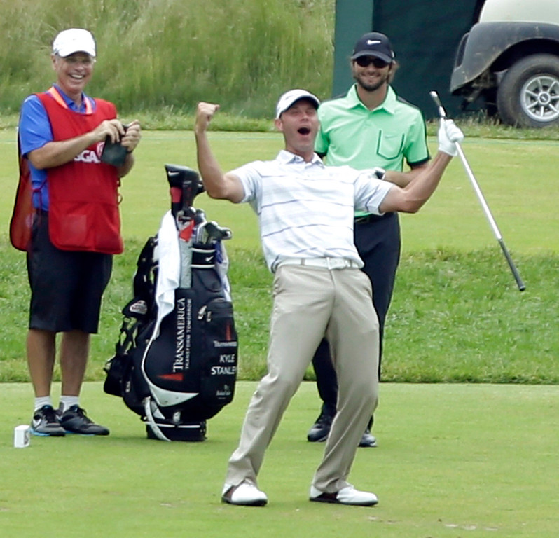 . Shawn Stefani, center, reacts after hitting a hole in one on the 17th hole during the fourth round of the U.S. Open golf tournament at Merion Golf Club, Sunday, June 16, 2013, in Ardmore, Pa. (AP Photo/Julio Cortez)