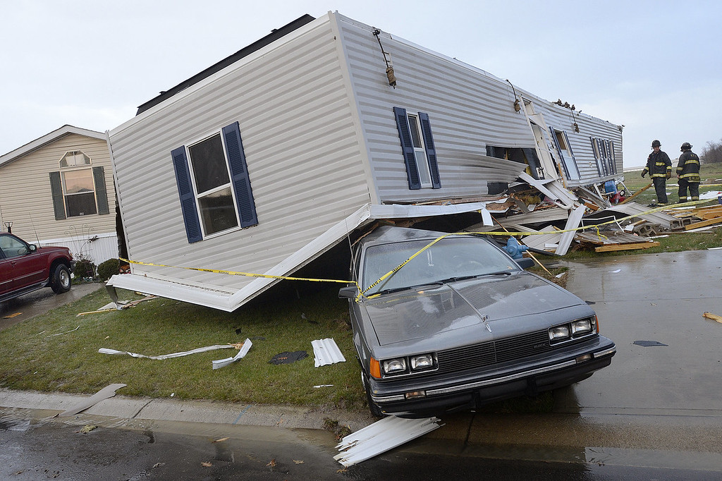 . Firefighters look over damage to trailers at Summit Village east of Marion, Ind., after storms blew through Marion and Grant County on Sunday afternoon, Nov. 17, 2013. (AP Photo/Chronicle-Tribune, Jeff Morehead)