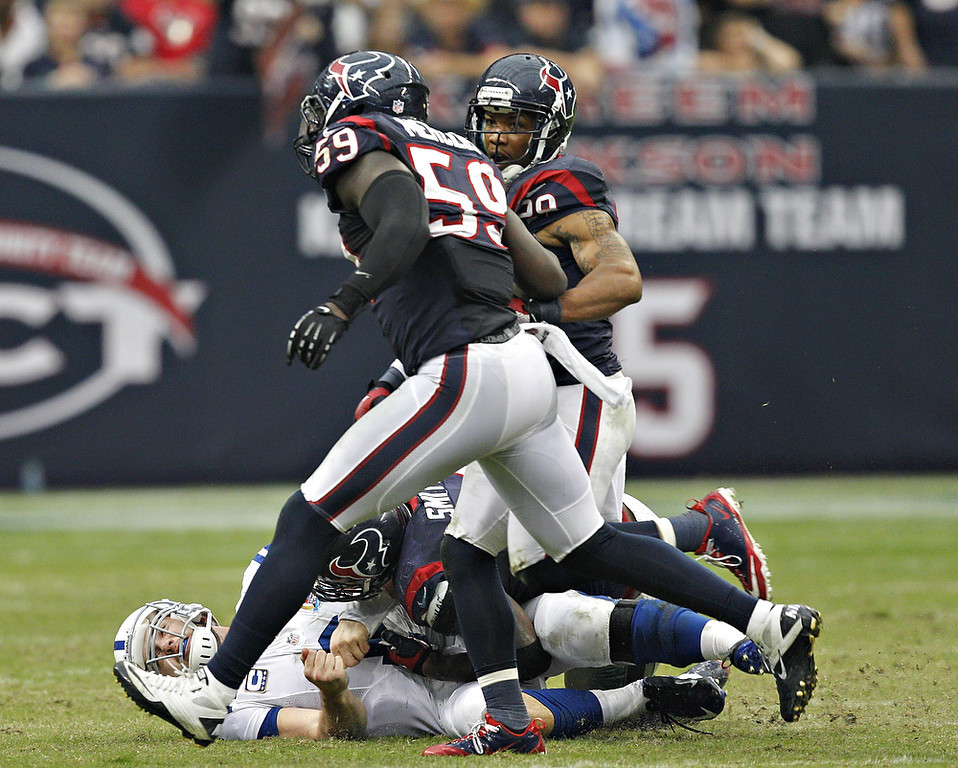 . Andrew Luck #12 of the Indianapolis Colts gets rid of the ball as he is tackled by Antonio Smith #94 of the Houston Texans in the second half at Reliant Stadium on December 16, 2012 in Houston, Texas. Texans win 29-17 to clinch the AFC South. (Photo by Bob Levey/Getty Images)
