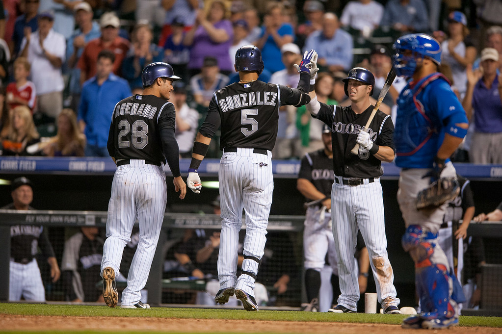 . DENVER, CO - AUGUST 06:  Carlos Gonzalez #5 celebrates a sixth inning two-run home run with teammates Nolan Arenado #28 and Corey Dickerson #6 of the Colorado Rockies in the sixth inning of a game against the Chicago Cubs at Coors Field on August 6, 2014 in Denver, Colorado.  (Photo by Dustin Bradford/Getty Images)