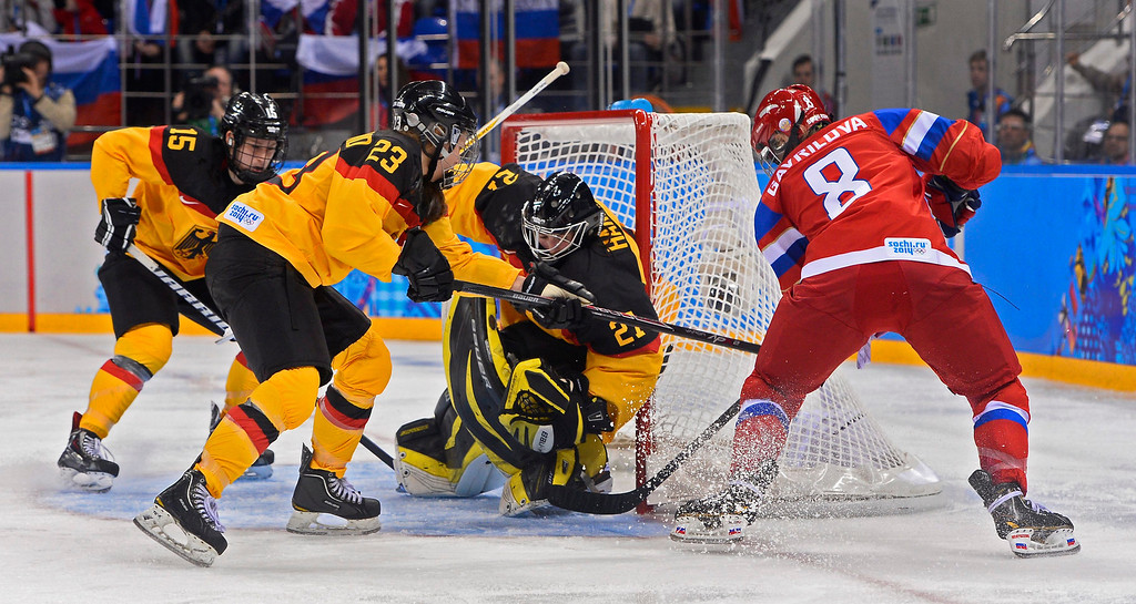 . Iya Gavrilova (R) of Russia scores a goal against Viona Harrer (CR) Tanja Eisenschmid (CL) and Andrea Lanzl (L) of Germany in the third period during their match in the Ice Hockey tournament at the Sochi 2014 Olympic Games in Sochi, Russia, 09 February 2014.  EPA/LARRY W. SMITH
