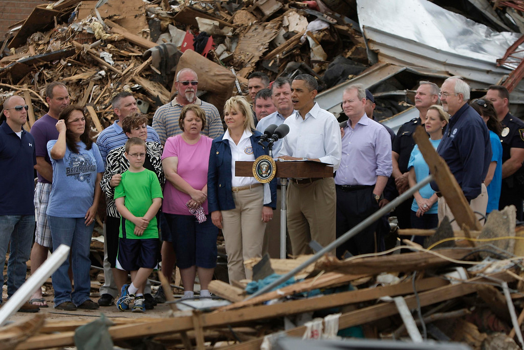. U.S. President Barack Obama stands with survivors and first responders as he speaks to reporters amidst the rubble of the tornado-destroyed Plaza Towers Elementary School in Moore, Oklahoma, May 26, 2013. Nearly one week ago a monster tornado ravaged the town, killing 24 people.  REUTERS/Jonathan Ernst