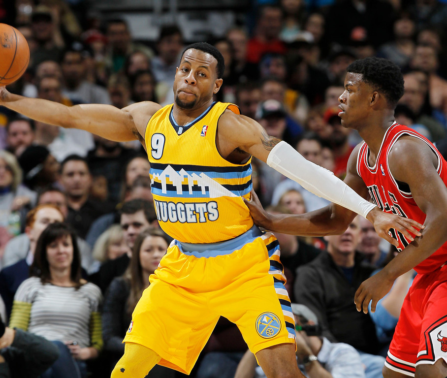 . Denver Nuggets guard Andre Iguodala, left, reaches out ot pull in a loose ball as Chicago Bulls guard Jimmy Butler covers in the first quarter of an NBA basketball game in Denver on Thursday, Feb. 7, 2013. (AP Photo/David Zalubowski)