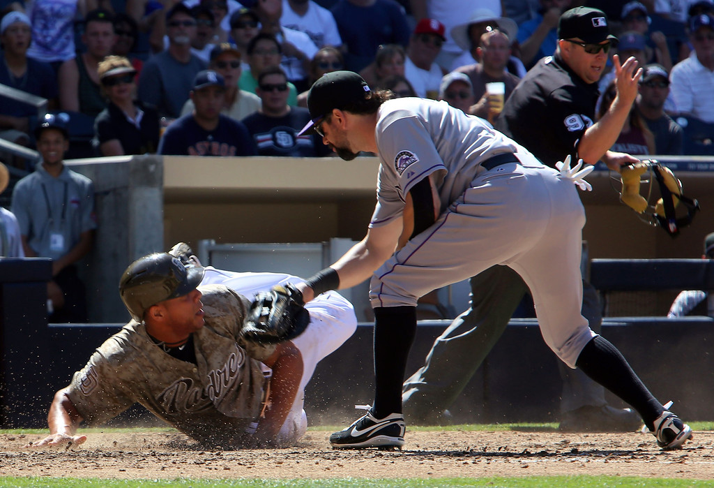 . Colorado Rockies first baseman Todd Helton, front right, puts a tag on San Diego Padres\' Kyle Blanks, left, at home as home plate umpire Todd Tichenor, back right, calls Blanks out for running outside of the baseline in the fifth inning during the baseball game on Sunday, Sept. 8, 2013, in San Diego. (AP Photo/Don Boomer)