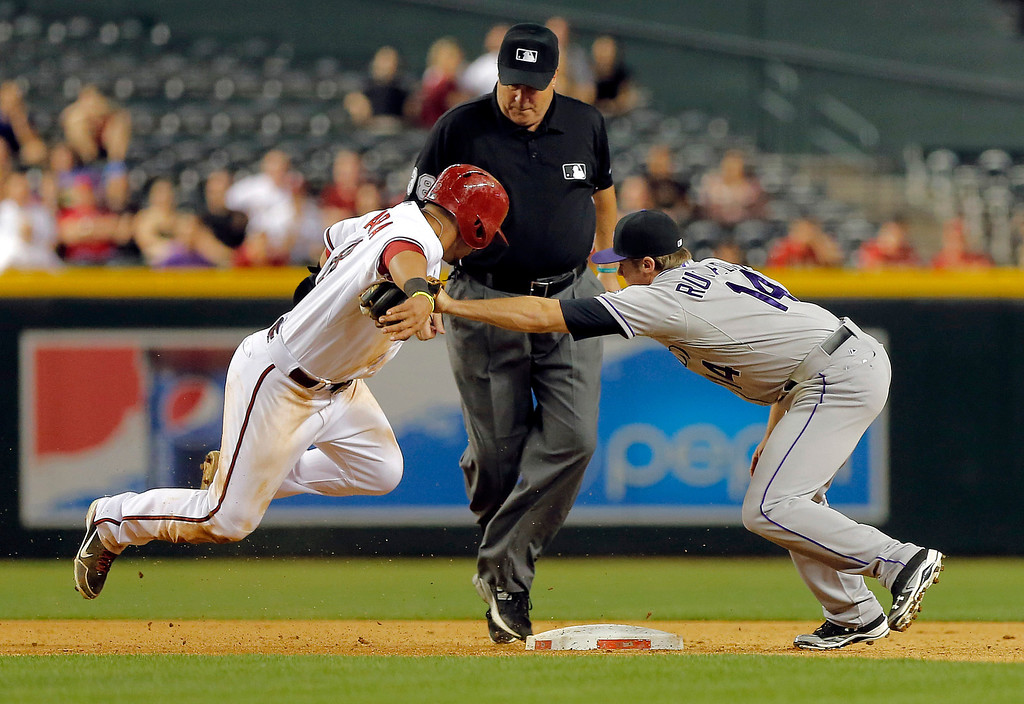 . Arizona Diamondbacks\' Gerardo Parra, left, tries to avoid the tag of Colorado Rockies\' Josh Rutledge while advancing on a fly out during the eighth inning of a baseball game, Thursday, April 25, 2013, in Phoenix. Umpire Lance Barksdale, rear, called Parra safe. (AP Photo/Matt York)