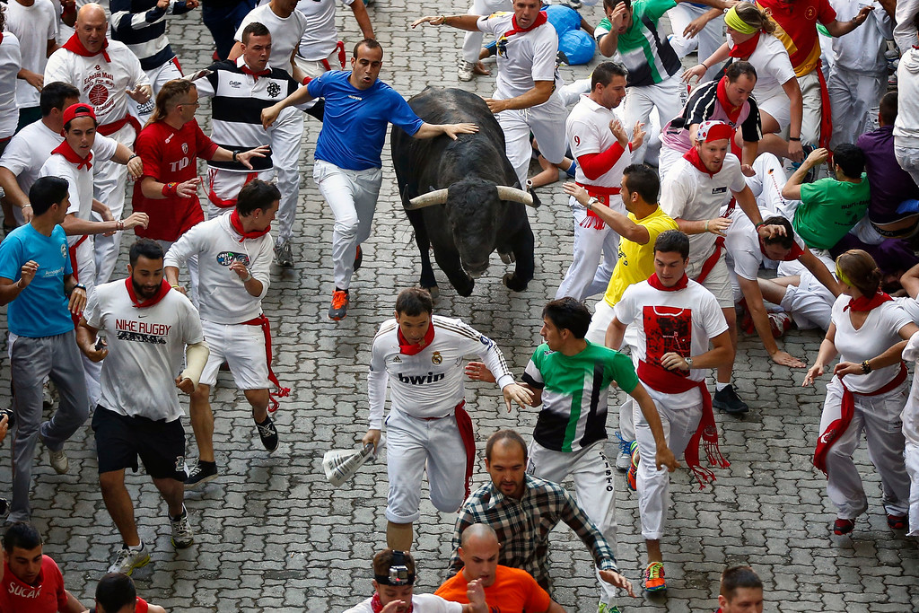 """. Revelers are chased by a Victoriano del Rio ranch fighting bull during the running of the bulls at the San Fermin festival, in Pamplona, Spain, Wednesday, July 10, 2013. Revelers from around the world arrive to Pamplona every year to take part in some of the eight days of the running of the bulls glorified by Ernest Hemingway\'s 1926 novel \""""The Sun Also Rises.\"""" (AP Photo/Daniel Ochoa de Olza)"""