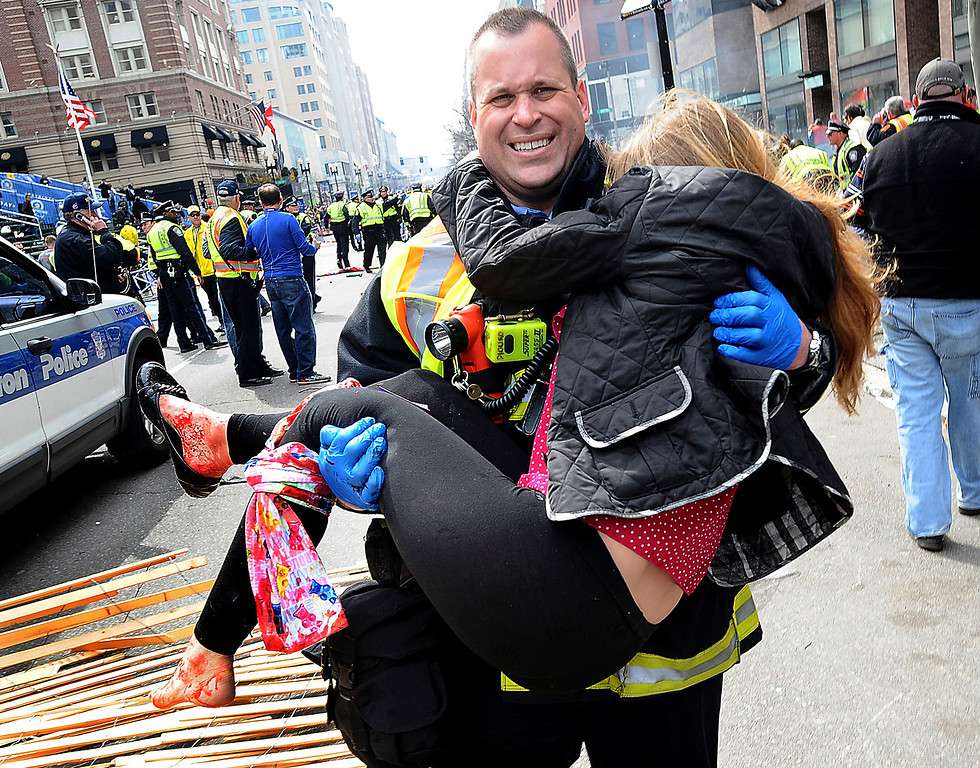 . In this Monday, April 15, 2013 photo, Boston Firefighter James Plourde carries an injured girl away from the scene after a bombing near the finish line of the Boston Marathon in Boston. The FBI\'s investigation into the bombings at the Boston Marathon was in full swing Tuesday, with authorities serving a warrant on a suburban Boston home and appealing for any private video, audio and still images of the blasts that killed at least three and wounded more than 170. (AP Photo/MetroWest Daily News, Ken McGagh)