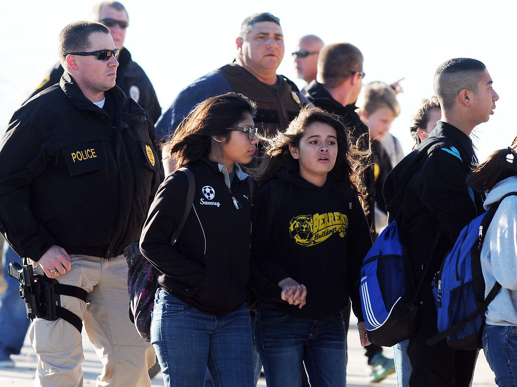 . Students surrounded by officials are escorted from Berrendo Middle School after a shooting, Tuesday, Jan. 14, 2014, in Roswell, N.M. Roswell police said the suspected shooter was arrested at the school, but authorities have not said if there were any injuries. The school has been placed on lockdown. No other details are yet available. (AP Photo/Roswell Daily Record, Mark Wilson)