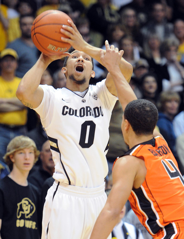 . Askia Booker of CU puts up a shot to beat the clock over Challe Burton of OSU during the first half of the March 9, 2013 game in Boulder.    (Cliff Grassmick/Boulder Daily Camera)
