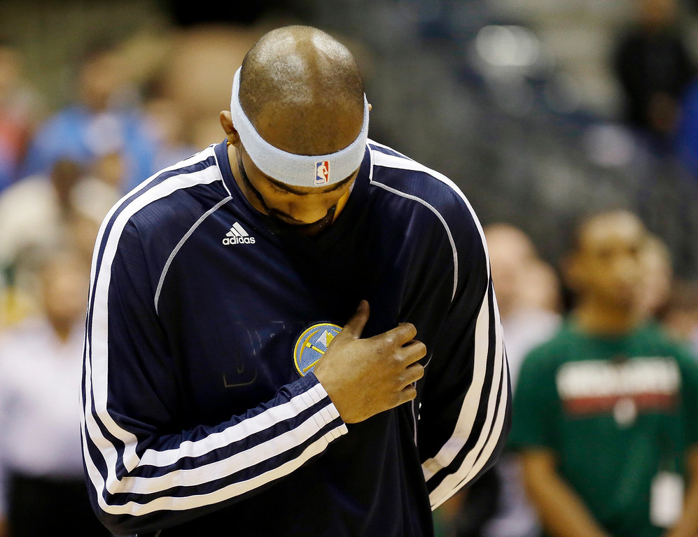 . Denver Nuggets\' Corey Brewer takes part in a moment of silence for the victims of the explosions at the Boston Marathon before their NBA basketball game against the Milwaukee Bucks, Monday, April 15, 2013, in Milwaukee. (AP Photo/Jeffrey Phelps)