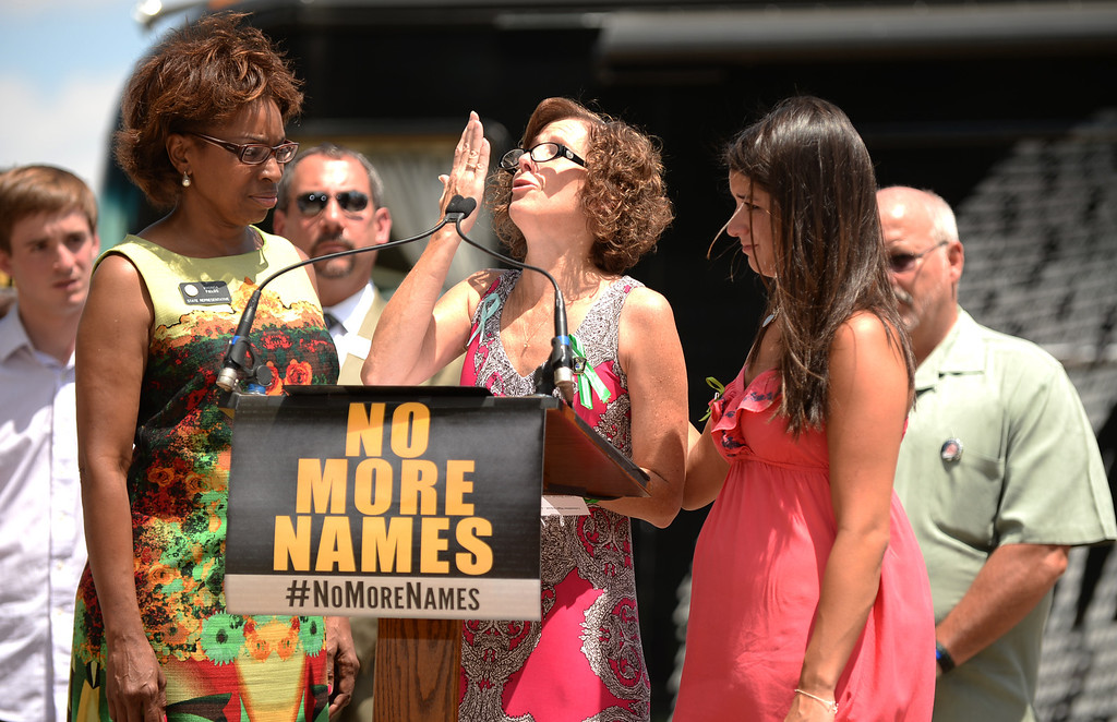 . AURORA, CO. - July 19: Jane Dougherty, whose sister Mary Sherlach, a psychologist at Sandy Hook Elementary School, was killed in the Newtown shooting, center, blows a kiss for her sister after reading the names of the Newtown shooting victims between Rep. Rhonda Fields, left, and Carlee Soto, whose sister Victoria, a teacher at Sandy Hook Elementary School, was killed in the Newtown shooting. The remembrance event for the one year anniversary of the Aurora theater shooting took place at Smokey Hill Shelter at Cherry Creek State Park. Aurora, Colorado. July 19, 2013.  Participants are reading the names of thousands of gun violence victims from across the country. Two groups met at the park to mark the first anniversary of the Aurora movie theater massacre � to one remember those killed by guns, and the other rally to support the Second Amendment. (Photo By Hyoung Chang/The Denver Post)