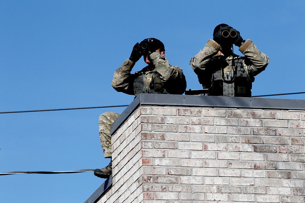 . Two police officers look on from a rooftop near the start area of the 118th Boston Marathon on April 21, 2014 in Hopkinton, Massachusetts.  (Photo by Alex Trautwig/Getty Images)