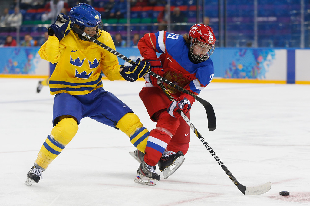 . Emilia Anderson of Sweden trips Anna Shokhina of Russia during the 2014 Winter Olympics women\'s ice hockey game at Shayba Arena, Thursday, Feb. 13, 2014, in Sochi, Russia. (AP Photo/Petr David Josek)