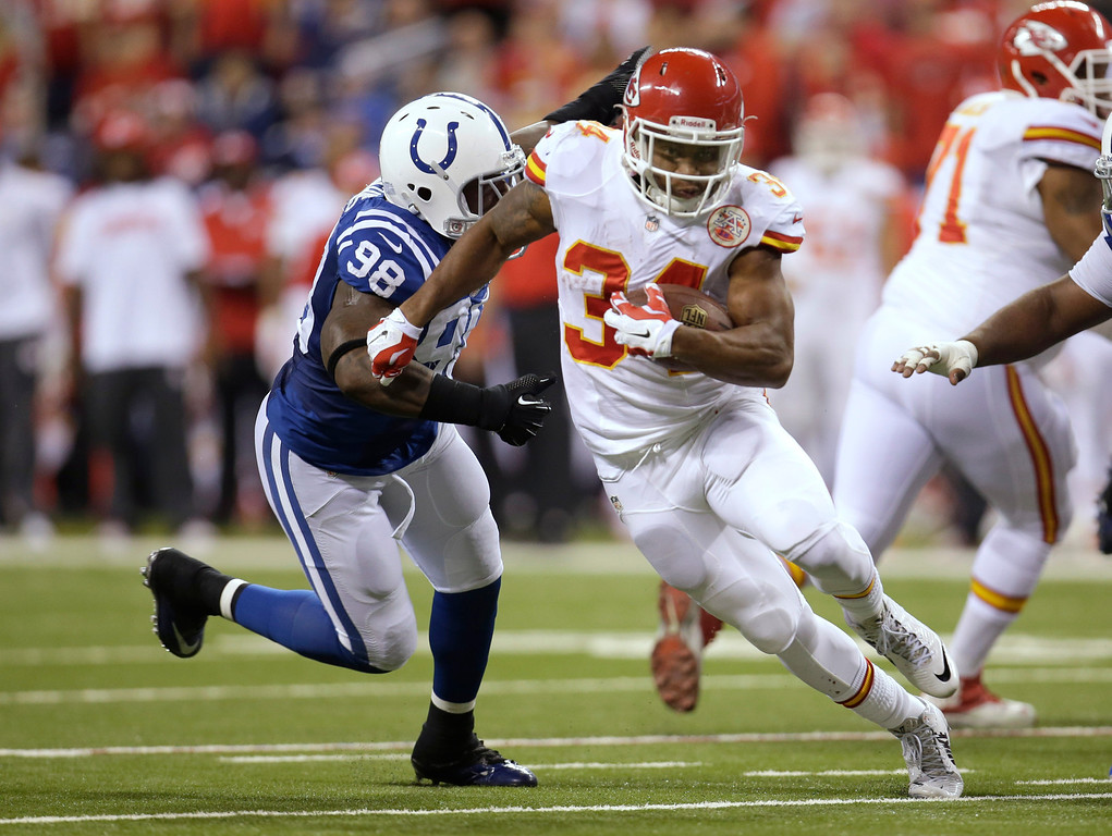 . Kansas City Chiefs running back Knile Davis (34) runs from Indianapolis Colts outside linebacker Robert Mathis (98) during the first half of an NFL wild-card playoff football game Saturday, Jan. 4, 2014, in Indianapolis. (AP Photo/AJ Mast)