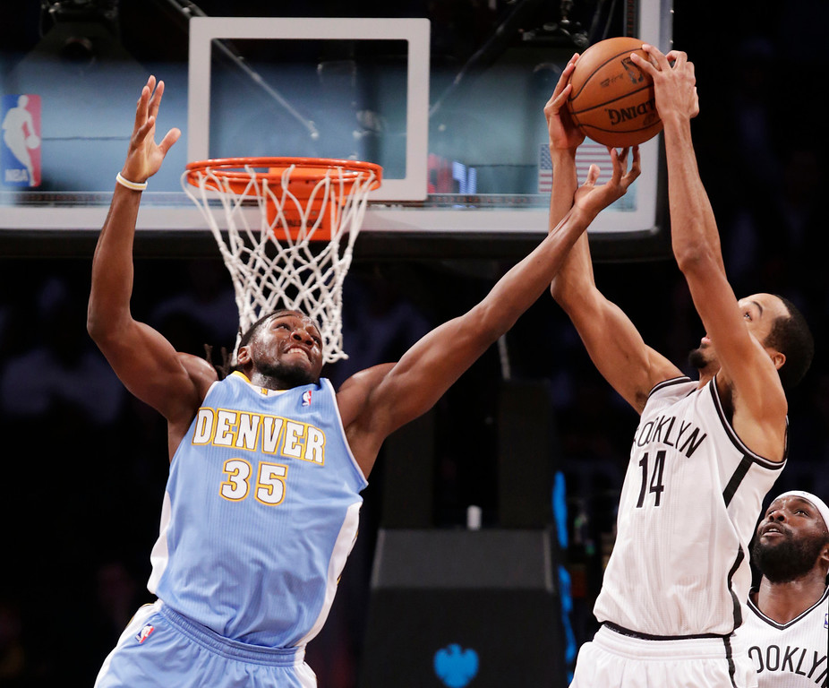 . Denver Nuggets forward Kenneth Faried (35) gets his fingers on the ball as Brooklyn Nets point guard Shaun Livingston (14) pulls down a rebound in the first half of an NBA basketball game Tuesday, Dec. 3, 2013, in New York. (AP Photo/Kathy Willens)