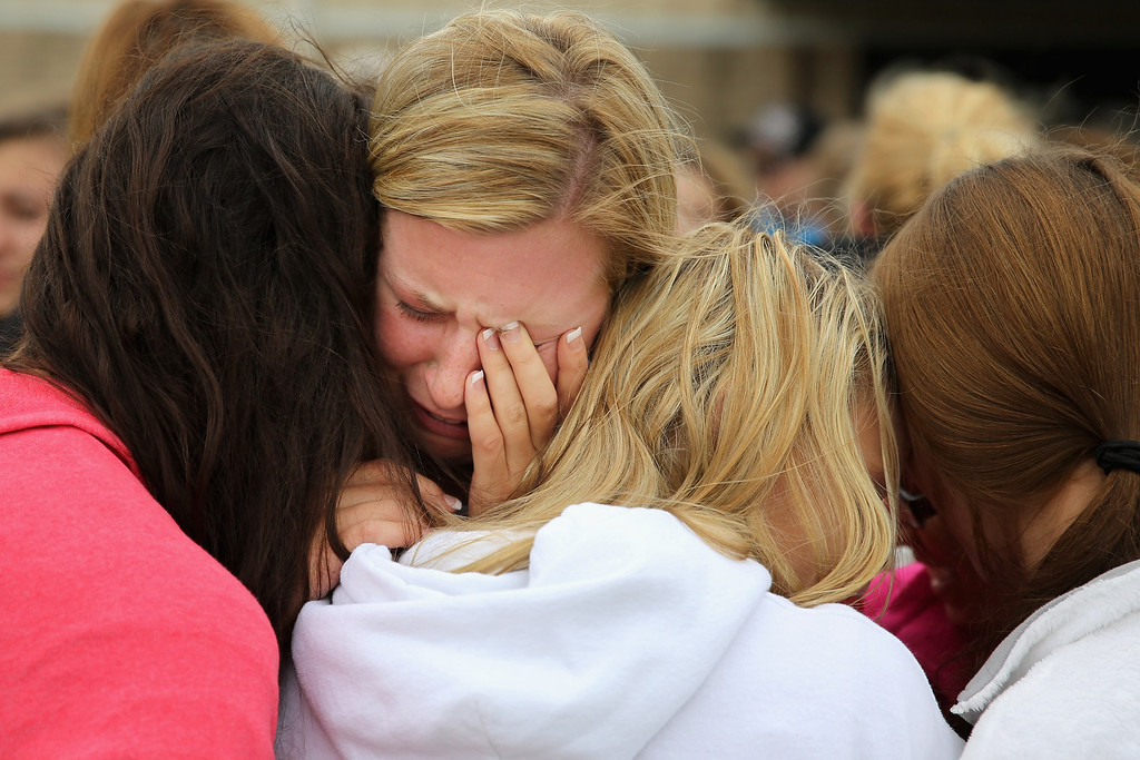 . WEST, TX - APRIL 18:  West High School senior Mackenzie Wernet (C) is embraced by fellow students and friends after praying for the victims and survivors the day after the West Fertilizer Company explosion April 18, 2013 in West, Texas. Wernet\'s home was destroyed when the fertilizer company caught fire and exploded, injuring more than 160 people and leaving damaged buildings for blocks in every direction.  (Photo by Chip Somodevilla/Getty Images)
