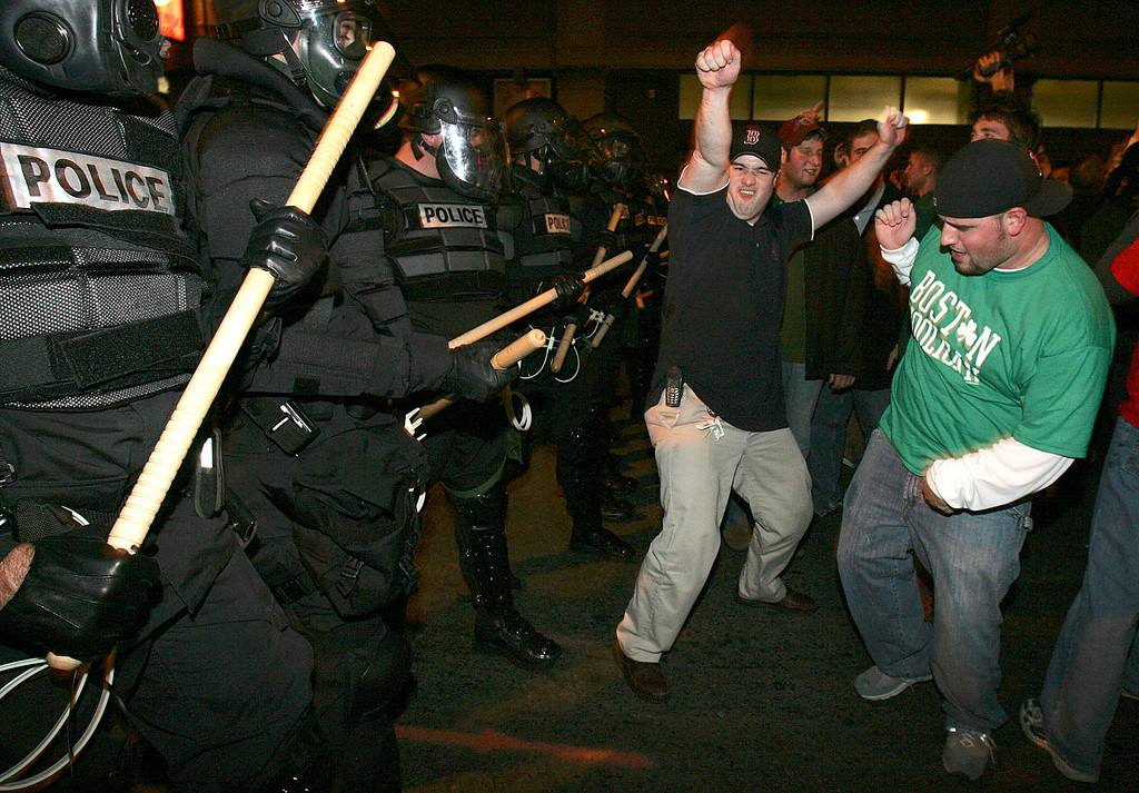 . Boston Red Sox fans celebrate in front of a line of riot police outside Fenway Park in Boston after the Red Sox beat the St. Louis Cardinals in the World Series Wednesday, Oct. 27, 2004. . (AP  Photo/Michael Dwyer)