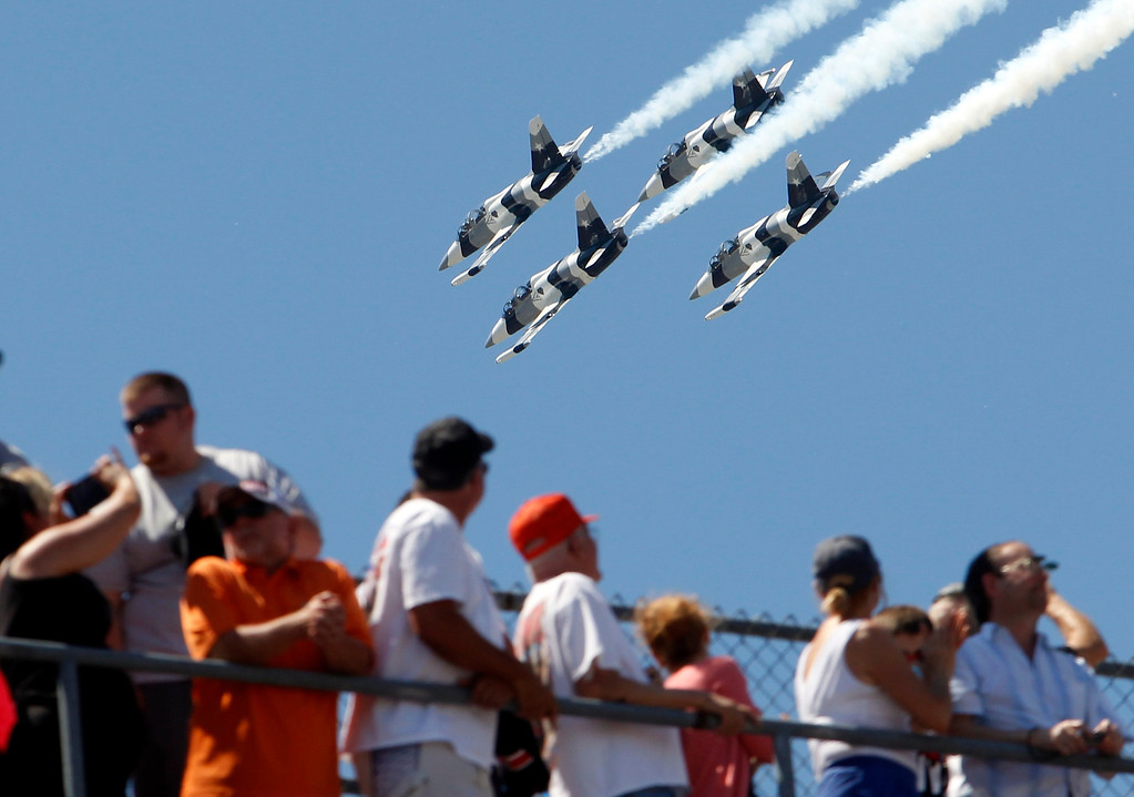 . Fans watch as four L-39 Albatros high-performance jet trainer aircraft  flown by the Black Diamond Jet Team, a civilian-owned aerobatic jet team perform a fly-over during the National Anthem before the start of the 98th running of the Indianapolis 500 IndyCar auto race at the Indianapolis Motor Speedway in Indianapolis, Sunday, May 25, 2014. (AP Photo/Tom Strattman)