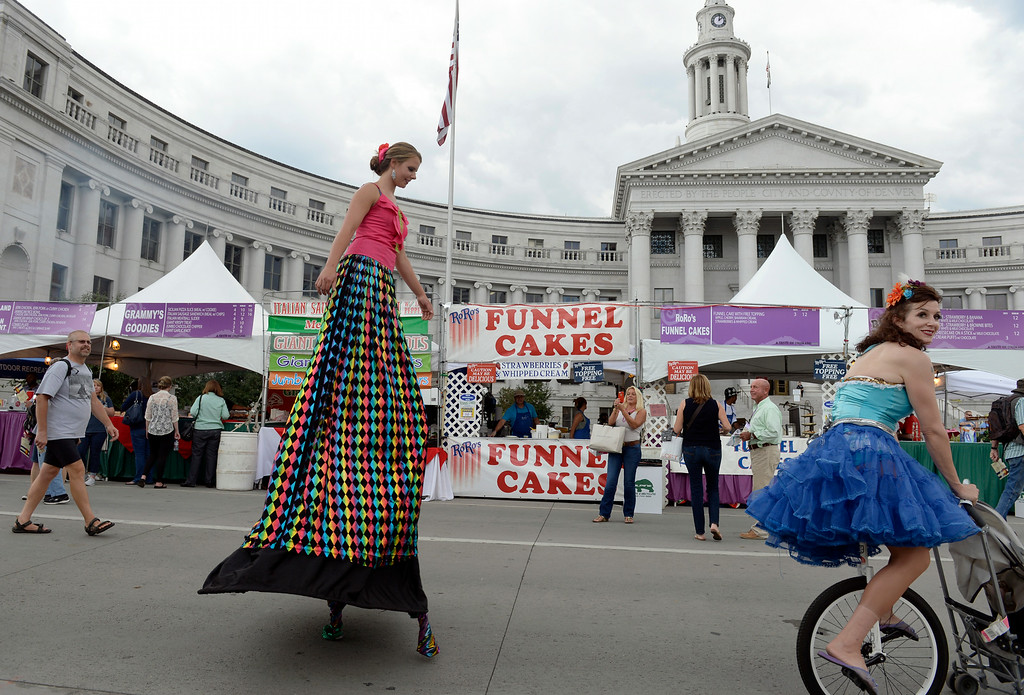 . DENVER, CO - AUGUST 29: Jasper Lau and Jennifer Dempsey, right, with the Salida Circus, greet visitors as they walk through the festival.  Hungry visitors make their way to the opening day of A Taste of Colorado at Civic Center Park in downtown Denver on Friday, Aug. 29, 2014. The food and music festival runs through Labor Day Weekend. (Kathryn Scott Osler/The Denver Post)