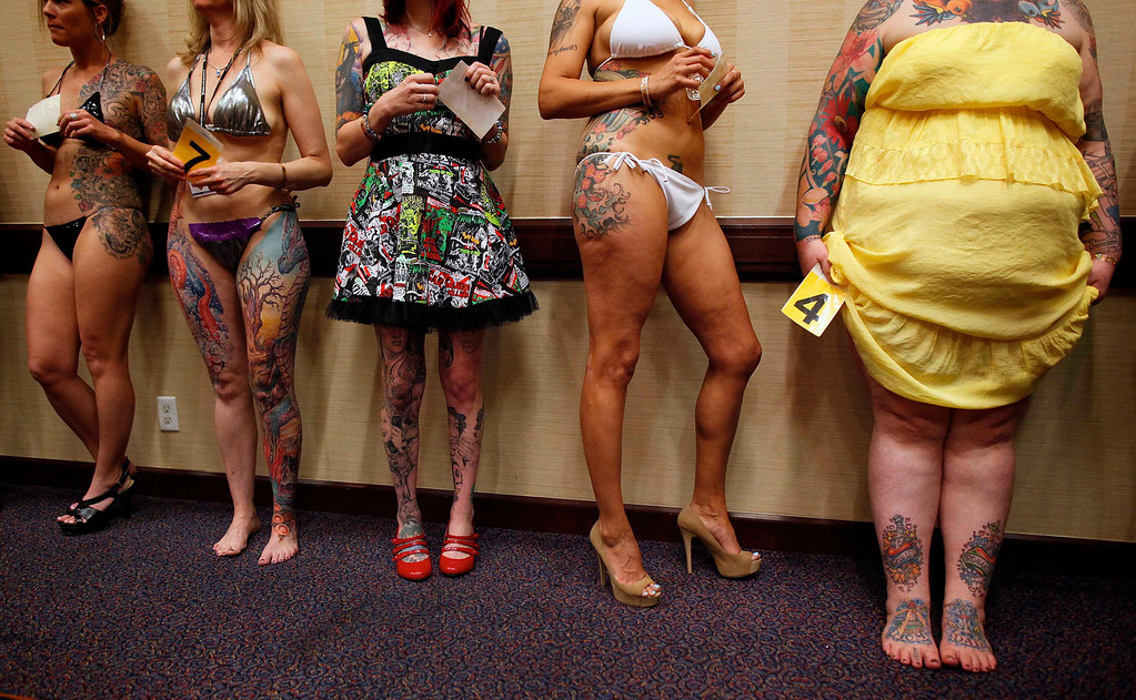 ". Keisha Holcomb (R), 31, from Fort Collins, Colorado, waits in line to have her tattoos judged in a contest during the National Tattoo Association Convention in Cincinnati, Ohio April 13, 2012. Holcomb, the product of a military family upbringing, was 16 when she got her first tattoo and is now a budding tattoo artist herself. She wants to have a full-body tattoo eventually, with the exception of her hands, throat and head. ""Try to keep it classy\"", she says.   REUTERS/Larry Downing"