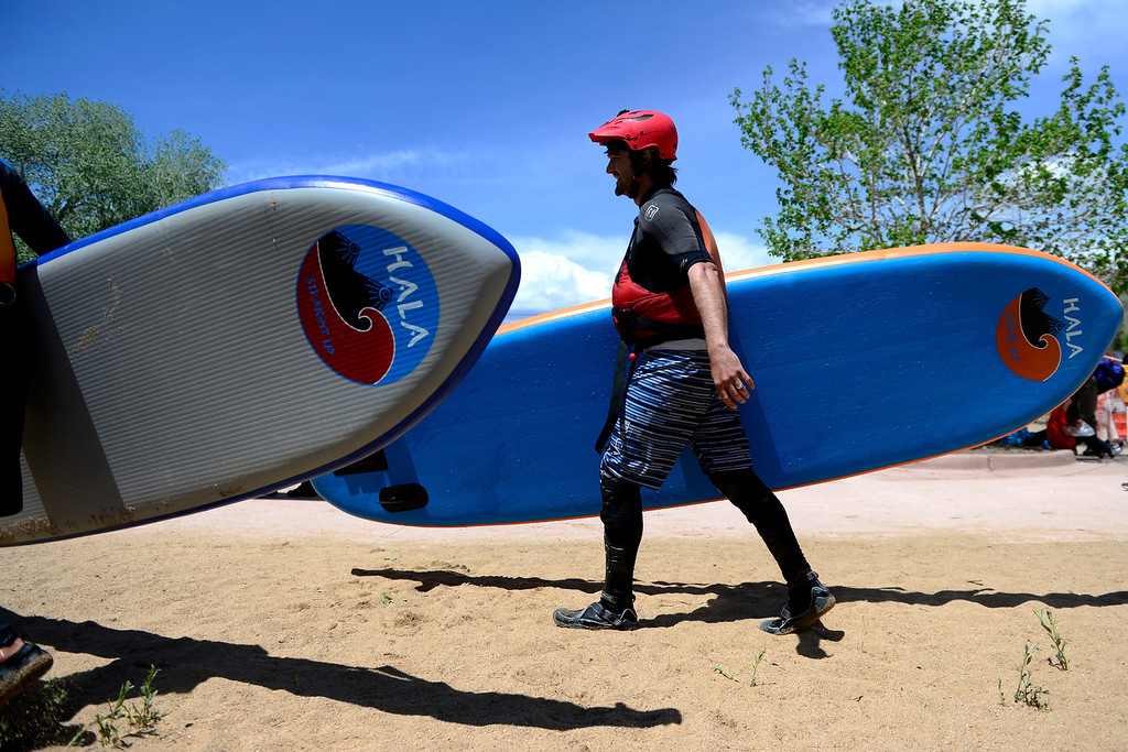 . Peter Hall carries his board during Golden Games at the Clear Creek Whitewater Park. (Photo by AAron Ontiveroz/The Denver Post)