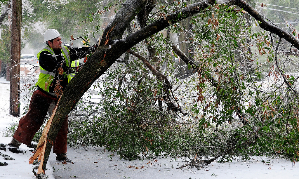 . A work crew cuts apart a fallen tree at Highland Avenue to clear the road on Wednesday, Feb. 12, 2014, in Augusta, Ga. Sleet, ice and fallen trees are prevail as a winter storm hits the Augusta area.   (AP Photo/The Augusta Chronicle, Sara Caldwell)
