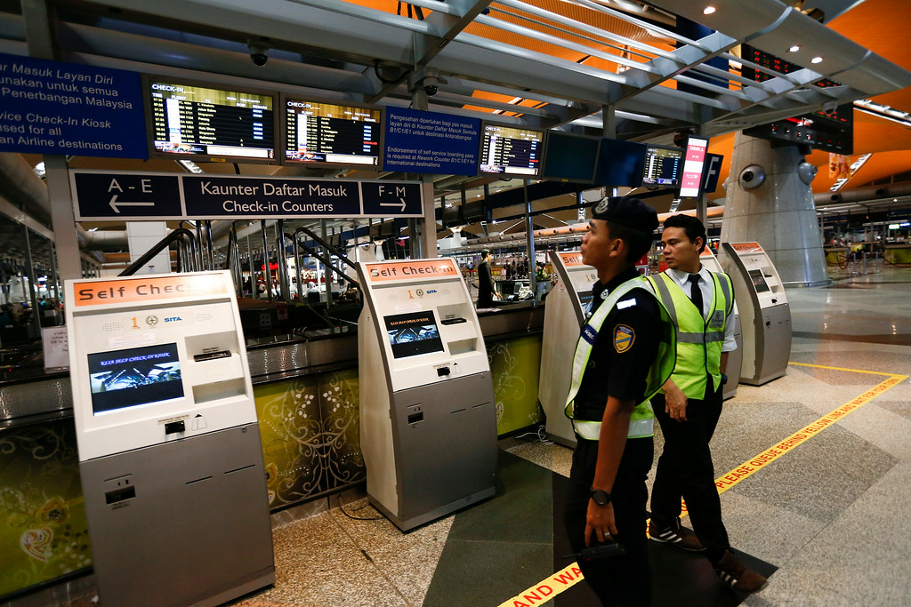 . Airport security personnel look at the flight information board in the departure hall, at Kuala Lumpur International Airport,  in Sepang, Malaysia, Friday, July 18, 2014.  Malaysia Airlines said it lost contact with Flight MH17 over Ukrainian airspace Thursday. It was flying from Amsterdam to Kuala Lumpur, Malaysia. (AP Photo/Vincent Thian)