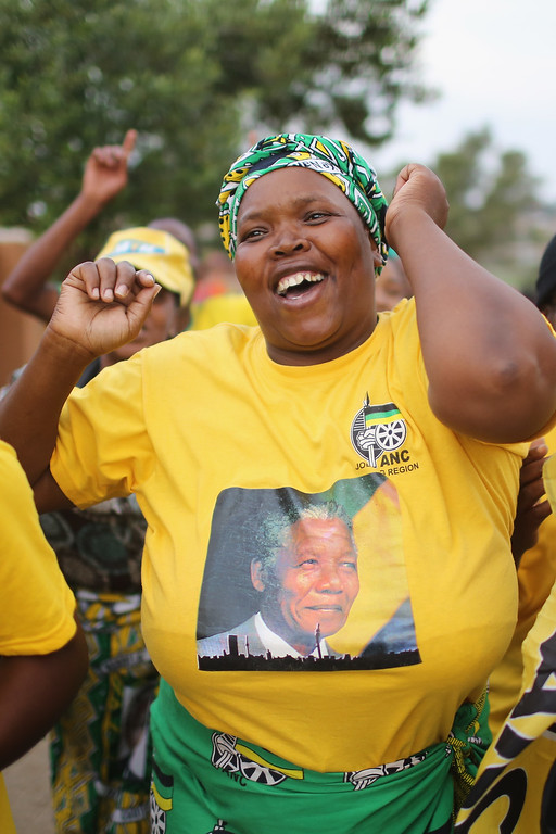. ANC supporters sing and dance to celebrate the life of Nelson Mandela outside his former home in Viliakazi Street, Soweto Township, on December 7, 2013 in Soweto, South Africa. Mandela, also known as Tata Madiba, passed away on the evening of December 5th at his home in Houghton at the age of 95. Mandela became South Africa\'s first black president after being jailed for decades for his activism against apartheid in a racially-divided South Africa. (Photo by Christopher Furlong/Getty Images)
