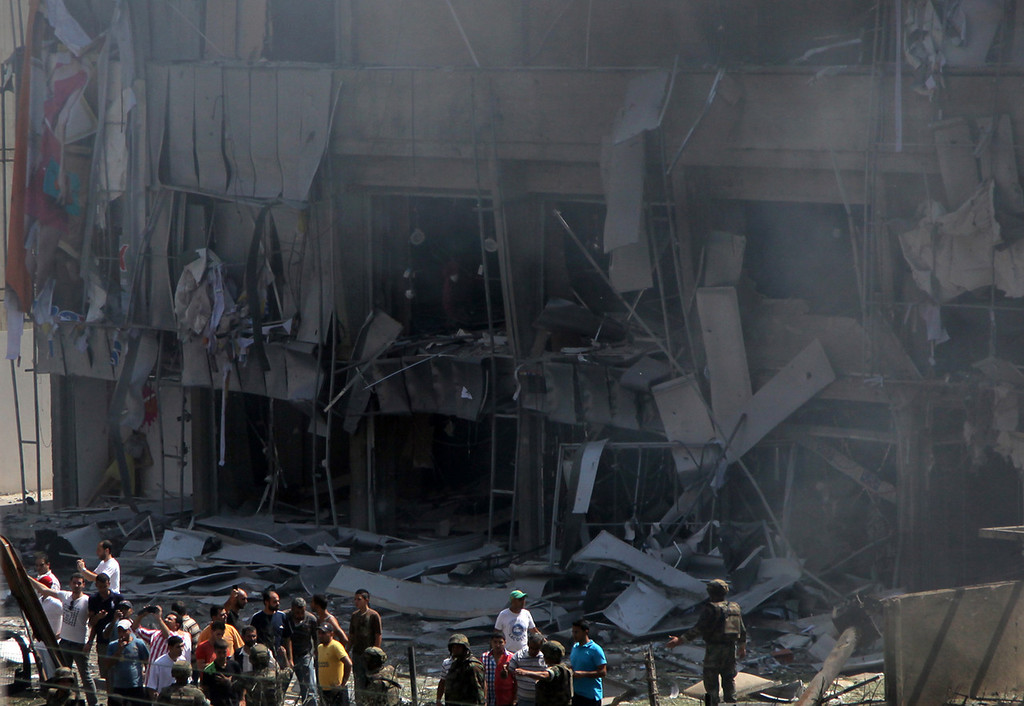 . Lebanese citizens stand in front of a severely damaged building as they gather outside al-Salam mosque, near the house of former Lebanese police chief Ashraf Rifi, at the site of a powerful explosion in the northern Lebanese city of Tripoli on August 23, 2013.  AFP PHOTO / STRSTR/AFP/Getty Images