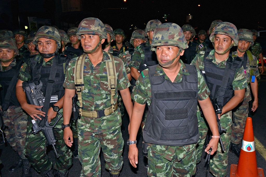 . Thai army soldiers advance through the city center after protesters hold an anti-coup rally on May 23, 2014 in Bangkok, Thailand. Anti-coup protesters rallied in Bangkok\'s shopping district, a day after the military seized control in a bloodless coup. Martial law imposes a 10pm to 5am curfew and public assembly is banned. (Photo by Rufus Cox/Getty Images)