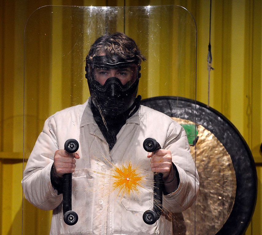 . Playing the part of a museum visitor, Andrew Parker is dressed in a protective coat, mask, and shield and tries to avoid getting hit by a paintball, but doesn\'t quite get out of the way in time. Parker and others are rehearsing their parts for running the Live-Show Dodge a Paint Ball exhibit. The Denver Museum of Nature and Science hosts MythBusters: The Explosive Exhibition which opens to the public Oct. 11 and  runs through Jan. 5, 2014. The exhibit uses interactive technology that allows visitors to spend the day as a MythBuster using the same methods as the hosts of Discovery Channel�s series MythBusters. Guest can experiment with Running in the Rain, Blind Driving, and Killer Card Toss. (Photo By Kathryn Scott Osler/The Denver Post)