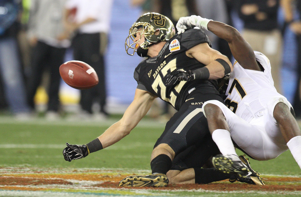 . Baylor\'s Clay Fuller drops a pass as he is hit by Central Florida\'s Brandon Alexander, right, during the Tostitos Fiesta Bowl at University of Phoenix Stadium in Glendale, Az., on January 1, 2014. (Joshua C. Cruey/Orlando Sentinel/MCT)