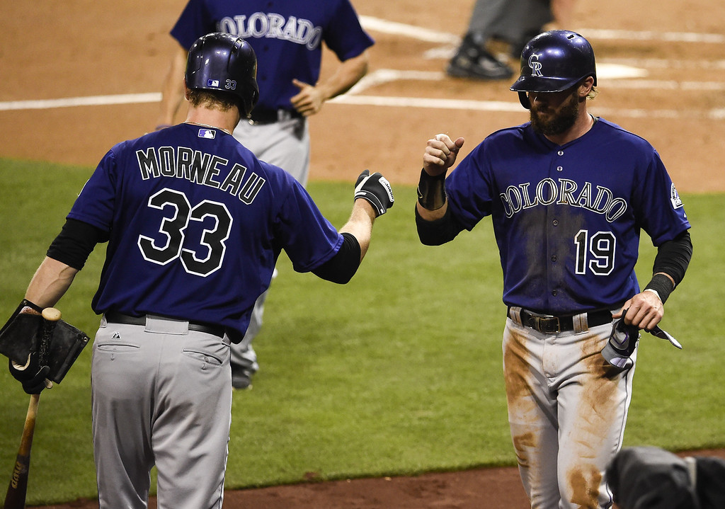 . Charlie Blackmon #19 of the Colorado Rockies, right, is congratulated by Justin Morneau #33 of the Colorado Rockies after scoring during the third inning of a  baseball game against the San Diego Padres at Petco Park April 14, 2014 in San Diego, California. The bad throw allowed a run to score.  (Photo by Denis Poroy/Getty Images)