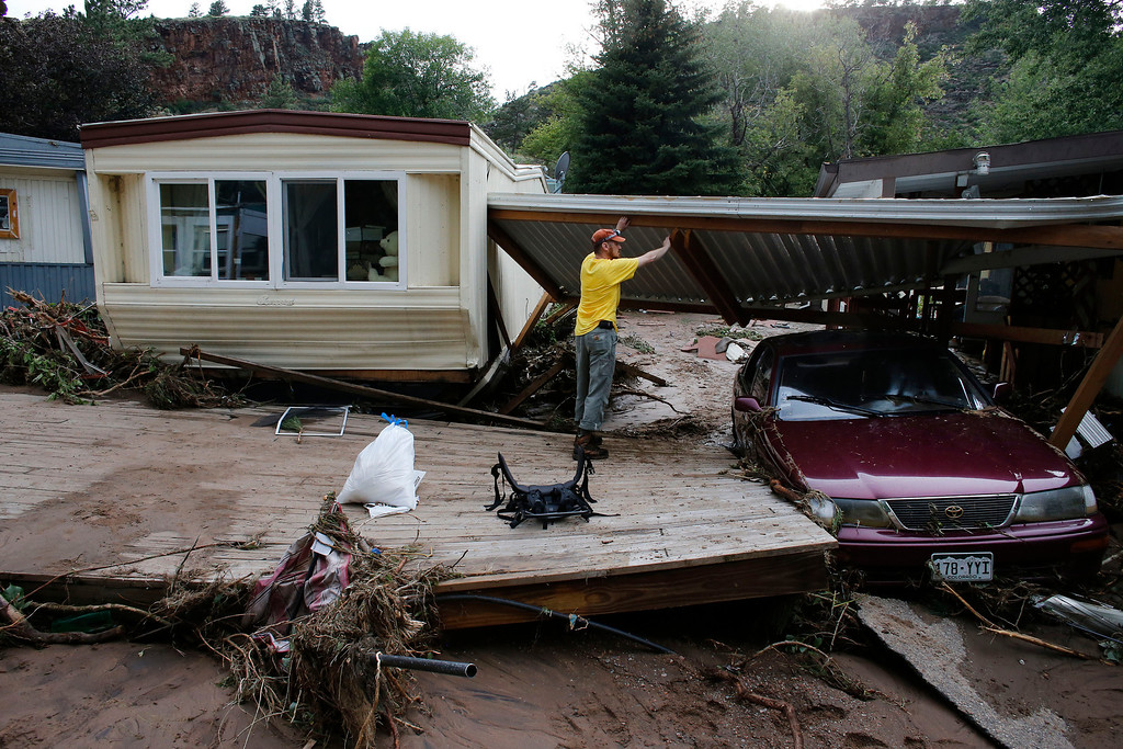 . Local resident Ben Rodman helps a friend salvage her home after floods left homes and infrastructure in a shambles, in Lyons, Colo., Friday Sept. 13, 2013. (AP Photo/Brennan Linsley)