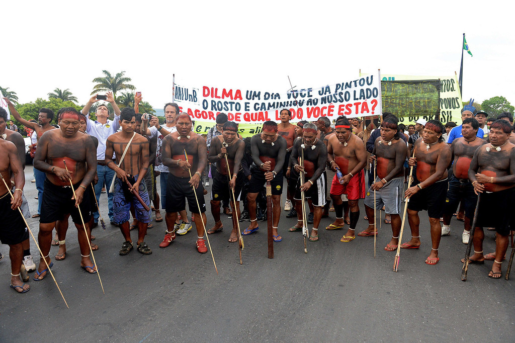 """. Indigenous people with a banner reading \""""Dilma, one day you painted your face and walked by our side. Now, on what side are you?\"""", dance in Brasilia on October 1, 2013, in the beginning of the National Indigenous Mobilization Week. Indigenous people from several ethnic groups will concentrate in the Brazilian capital to demand more support from the federal government during the week. AFP PHOTO / Evaristo SA/AFP/Getty Images"""