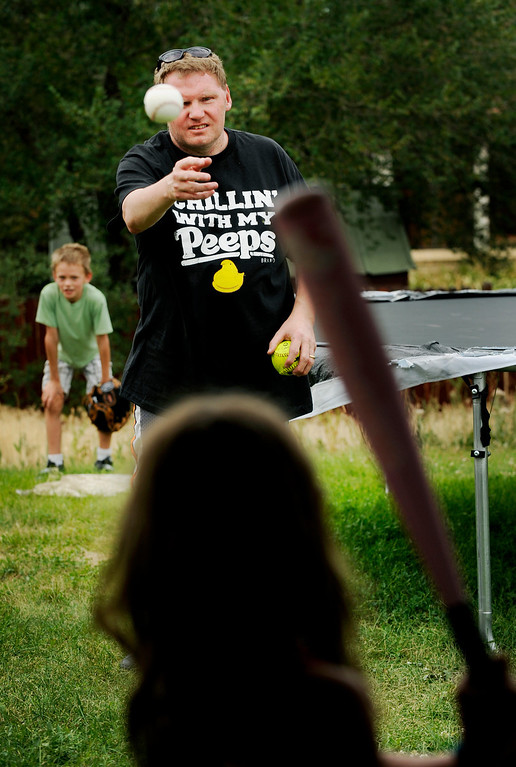 . Brent, an avid sports fan, center, squints as he plays baseball with his two oldest children, Gavin, 9, background, and Sienna, 8, who both move around to accommodate their father\'s very few bad pitches. The father of five doesn\'t allow his retinitis pigmentosa - a condition that\'s left him with about 30 percent tunnel vision and zero peripheral vision - to limit his daily activities, especially when it comes to his kids.  Photo by Jamie Cotten, Special to The Denver Post